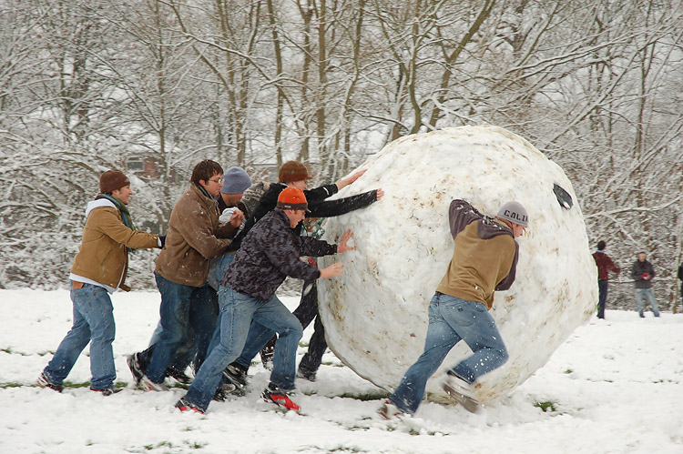 A group of people rolling a snowball taller than any of them
