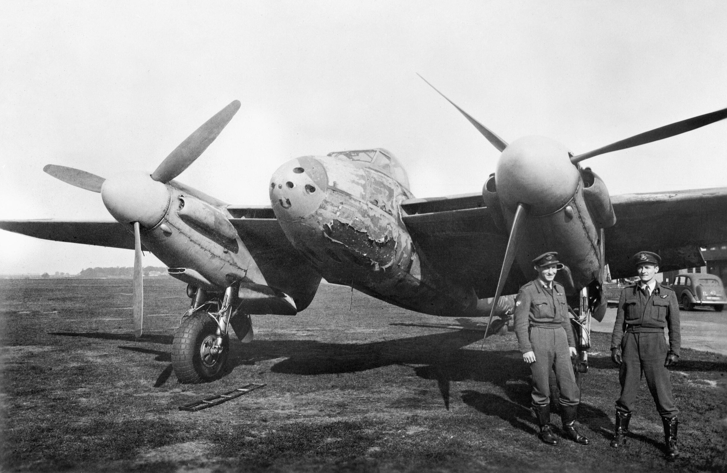 Flight Lieutenant M Cybulski (left) and Flying Officer H Ladbrook of No. 410 Squadron RCAF, with their damaged Mosquito Mk II at Coleby Grange, 27 September 1943. Their aircraft was severely charred by an explo CE106