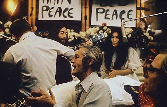 "Lennon and Ono sit in front of flowers and placards bearing the word ""peace."" Lennon is only partly visible, and he holds an acoustic guitar. Ono wears a white dress, and there is a hanging microphone in front of her. In the foreground of the image are three men, one of them a guitarist facing away, and a woman."