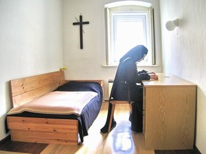 English: A Discalced Carmelite nun sits in her...