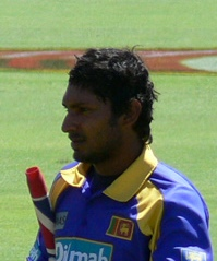 Portrait picture of a dark skinned man wearing blue and yellow Sri Lankan cricket kit, with a partially visible cricket bat under his arm.
