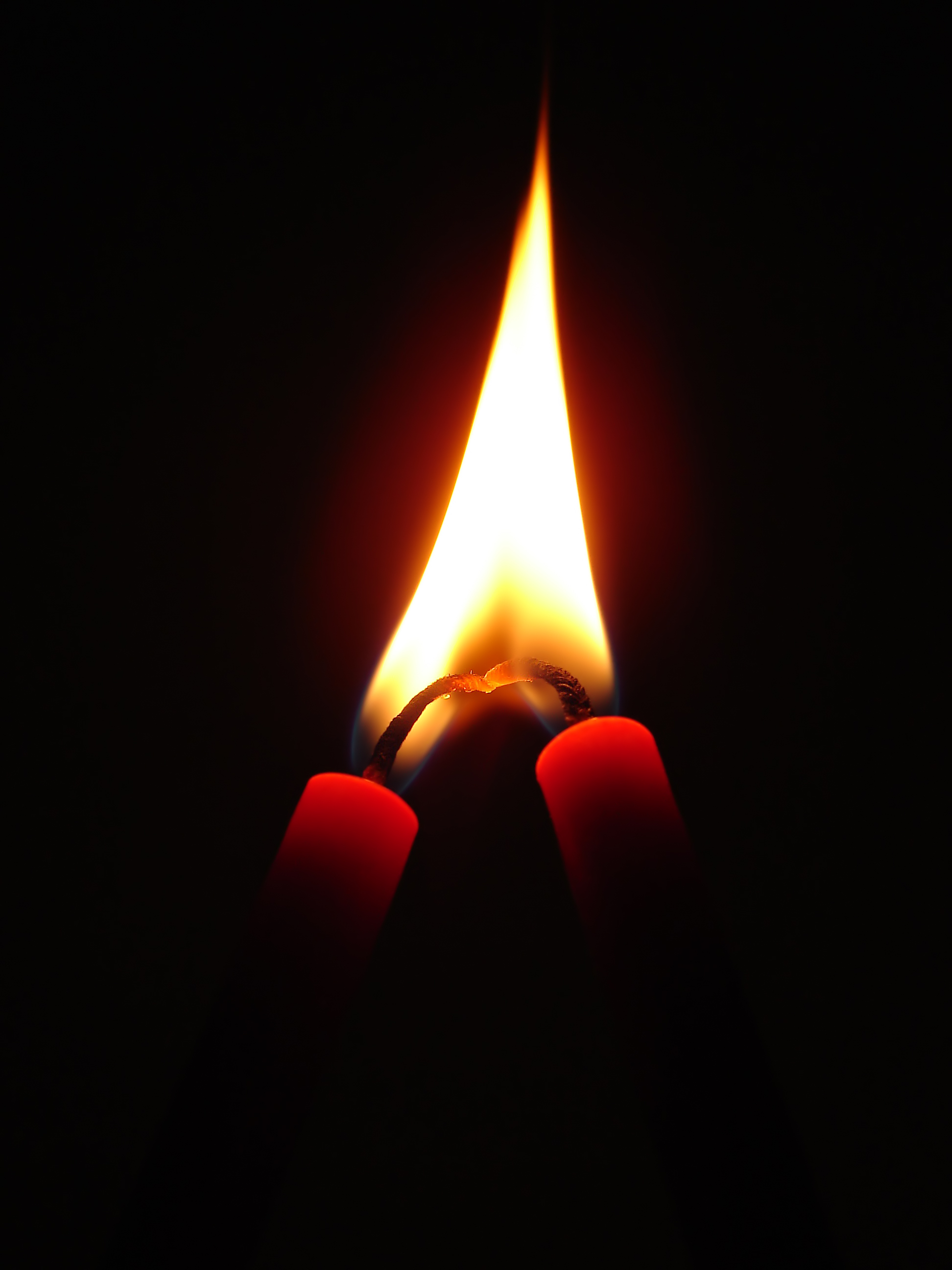 English: Two candles in love. The flame is inv...