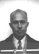 "Head and shoulders mug shot of middle-aged man in suit and tie. Lettering reads ""C 16"""