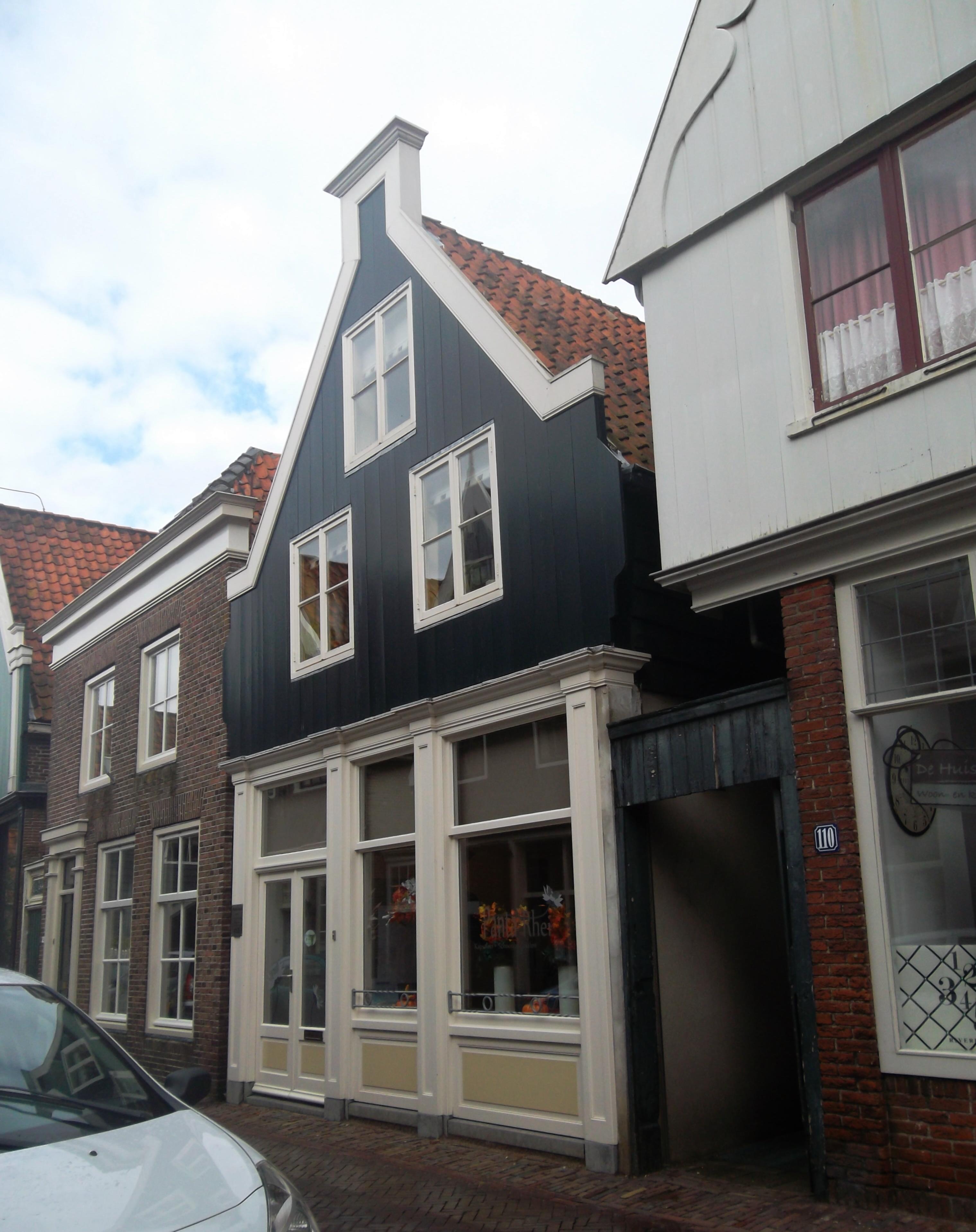 Huis met zadeldak en houten topgevel op geprofileerde for Lijst inrichting huis