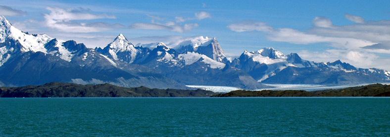 Vista de la cordillera de los Andes desde las llanuras del parque nacional Los Glaciares, la vista es desde la playa oriental de uno de los grandes valles glaciares de la Patagonia argentina, si se observa más allá del lago y de la franja boscosa y aquende a la cordillera se pueden notar a la distancia dos lenguas de glaciares que desembocan en los lagos tras bajar de las montañas siempre nevadas.