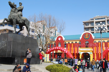 Xiangying Square in the center of Jinzhou, with Guan Xiangying's statue (left) and the former Museum turned a drugstore (back).