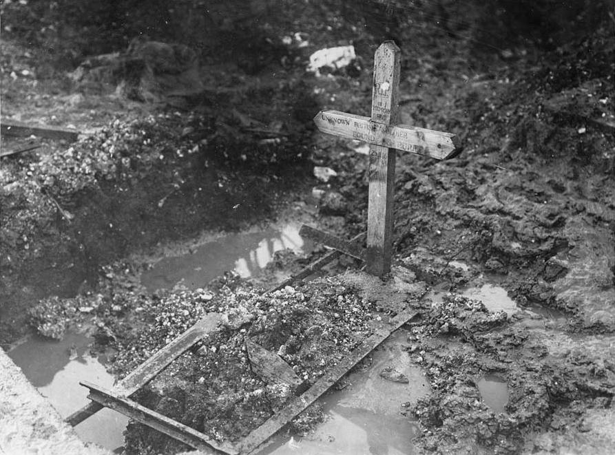 A grave outlined by a few sticks in a muddy puddle. A simple cross bears the date 25 November 1916 and the inscription, 'RIP unknown British Soldier found buried'. Many men who died were never identified.Each of the countries involved in the war chose one of their unknown dead soldiers to represent the many who were never identified or whose bodies were never found. In Britain, the unknown soldier is buried in Westminster Abbey. [Original reads: 'Grave of an unknown British soldier.'] http://digital.nls.uk/74549294