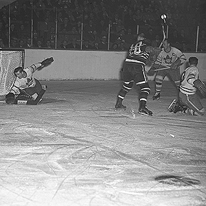 It is ice-level during action of a hockey game. A goal-tender reaches down with his blocker to stop a puck. An opposition forward and two of his own players are in front of his net.