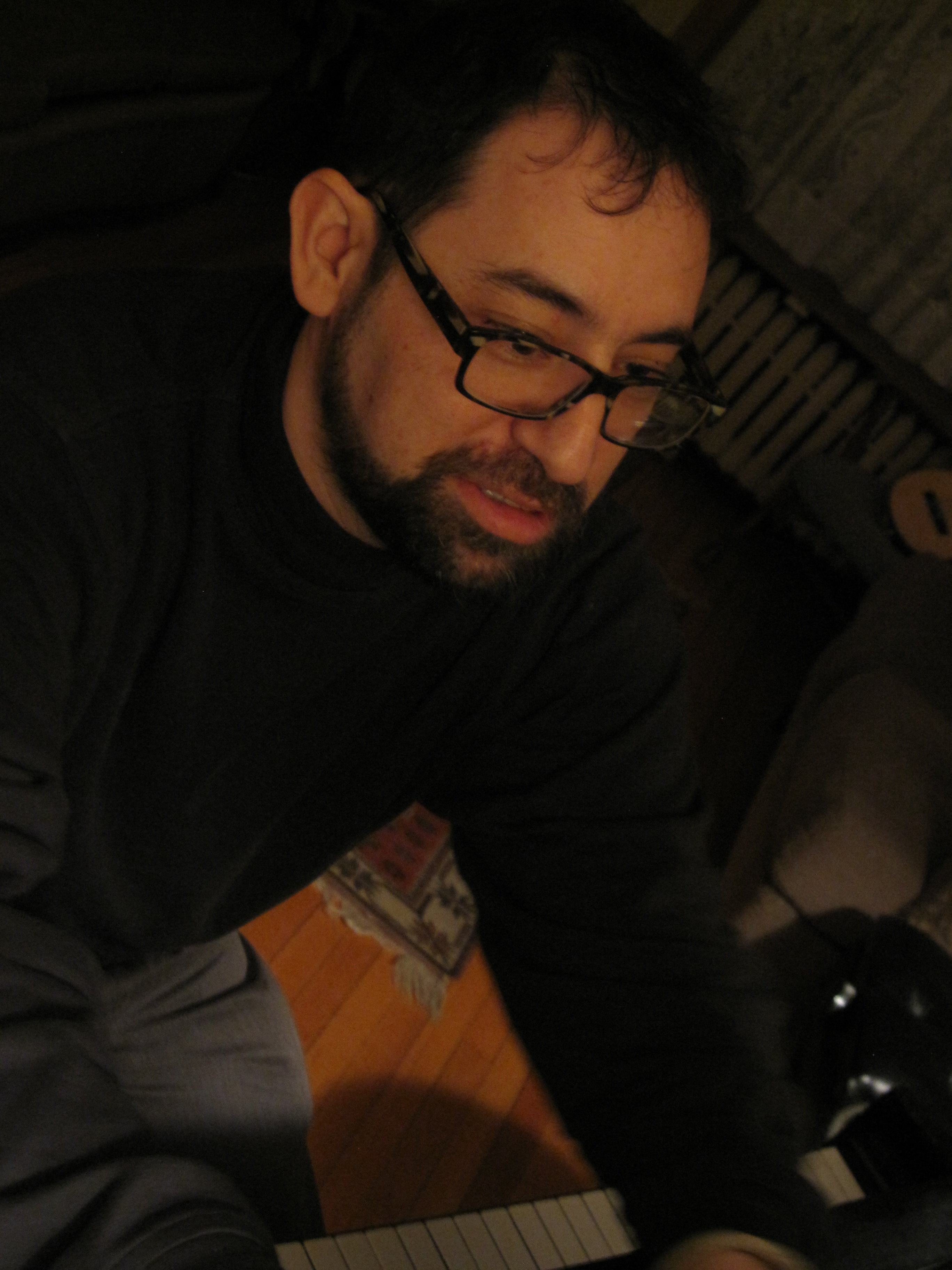 Rick Perlstein at a piano, selecting music to play from a book of jazz standards, Chicago, March 2013.