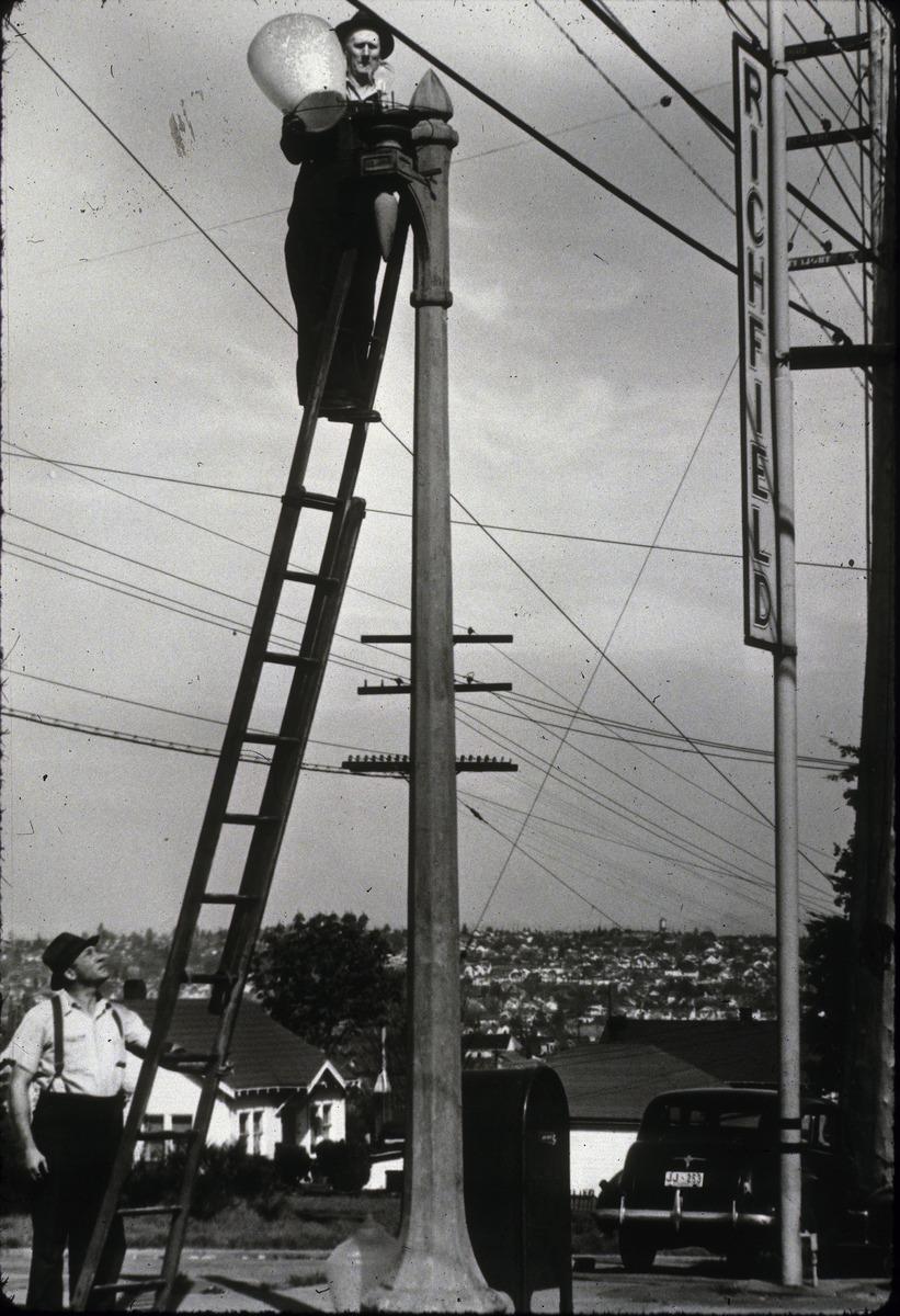 File:Seattle City Light worker changing streetlight, circa 1930s jpg