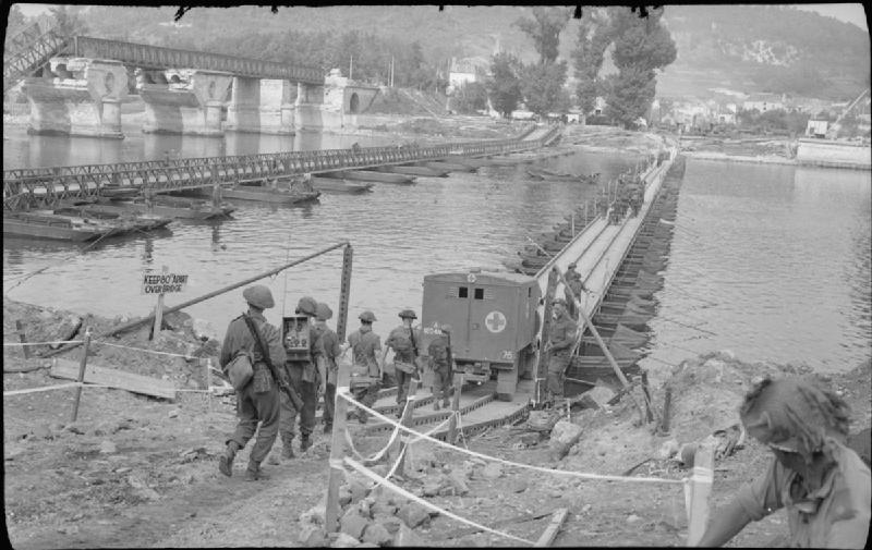 An ambulance and infantry crossing the river