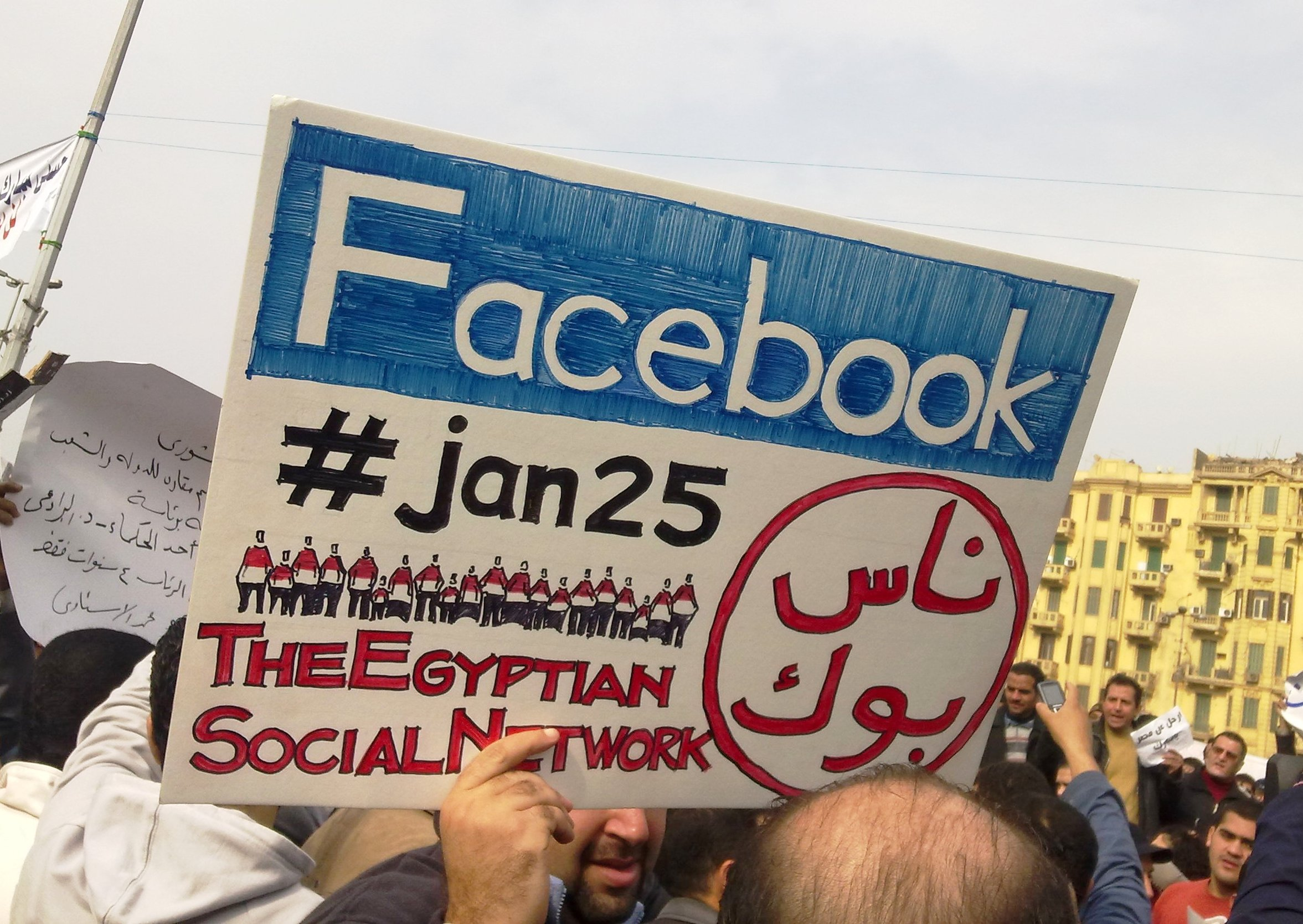"A man during the 2011 Egyptian protests carrying a card saying ""Facebook,#jan25, The Egyptian Social Network""."