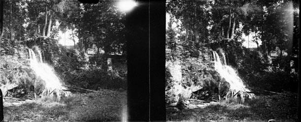 """Fonds Trutat - Photographie ancienne  Cote: TRU C 2197 Localisation: Fonds ancien (S 30)  Original non communicable  Titre: Cascade dans la cour  au Castelet, 14 juillet 1906  Auteur: Trutat, Eugène Rôle de l'auteur: Photographe  Lieu de création: Perles-et-Castelet (Ariège) Date de création: 1906  Mesures:: 4,5 x 5,5 cm  Observations:  Deux plaques. Note manuscrite de Trutat: """" au Castelet, cascade dans la cour, 14 juillet 1906, Goerz """".  Mot(s)-clé(s):  -- Cascade -- Eau -- Versant rocheux -- Rocher -- Cour -- Arbre  -- Perles-et-Castelet (Ariège) -- Ax-les-Thermes (Ariège; canton) -- Ariège (France; vallée) -- Ariège (Midi-Pyrénées)  -- 20e siècle, 1e quart  Médium: Photographies -- Négatifs sur plaque de verre -- Noir et blanc -- Paysages -- Goerz   Voir:  TRU C 2196 Cascade au Castelet, 14 août 1906 TRU C 2548 B Cascade au Castelet, 14 août 1906   numerique.bibliotheque.toulouse.fr/cgi-bin/library?c=phot...  Bibliothèque de Toulouse. Domaine public"""