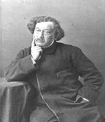 A man with medium-length hair rests against a table, a finger pressed against his right cheek.