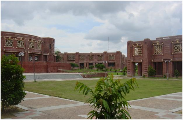 Grassy quadrangle in front of low, red buildings