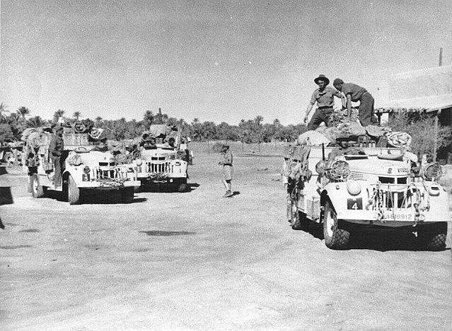 three trucks overloaded with supplies and six men in the foreground. The trees of the oasis can be seen in the background