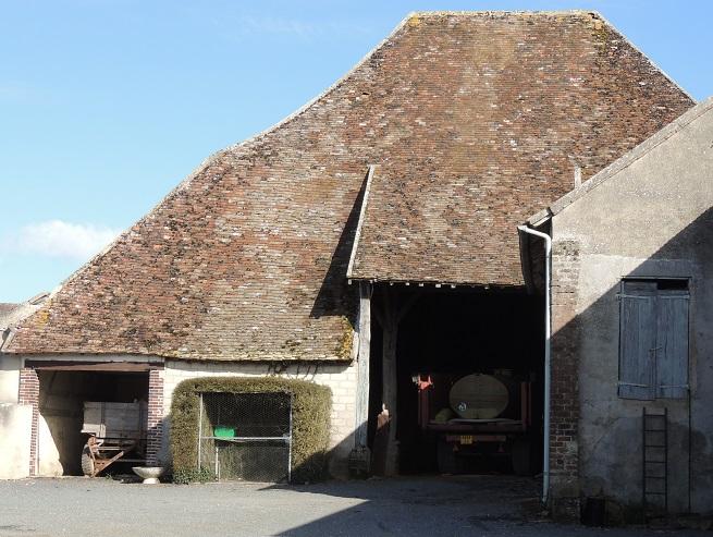 """Grange dîmière de Malesherbes à Montigny le Guédier avec un grand toit à faitage central très court et donc à pentes d'environs 45° avec différentiel pour la grande """"porte"""" où il est moins pentu et pour le reste du batiment où il court jusqu'aux murs d'à peine plus d'1 m de haut. Les arretes de ce grand toit ne sont pas rectilignes Un autre profil de batiment sur la droite cache la partie droite de la grande """"porte"""""""