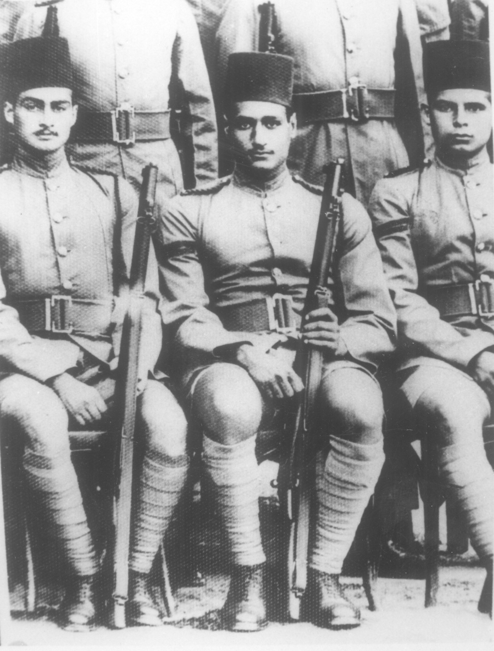 Two seated men in military uniform and wearing fez hats