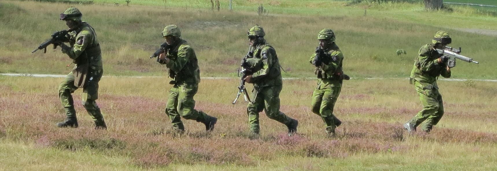 Foto av svenska soldater som framrycker över fält i grupp.