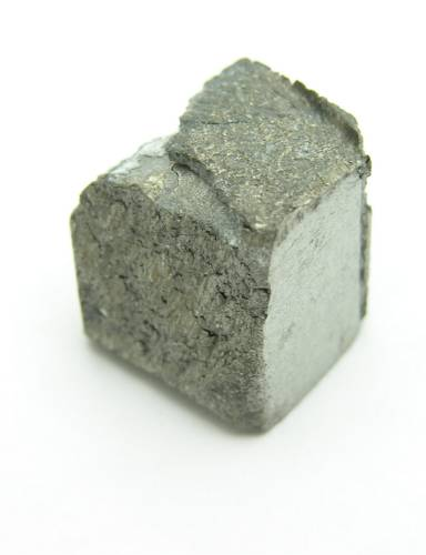 Roughly cube shaped piece of dirty grey metal with an uneven superficial structure.