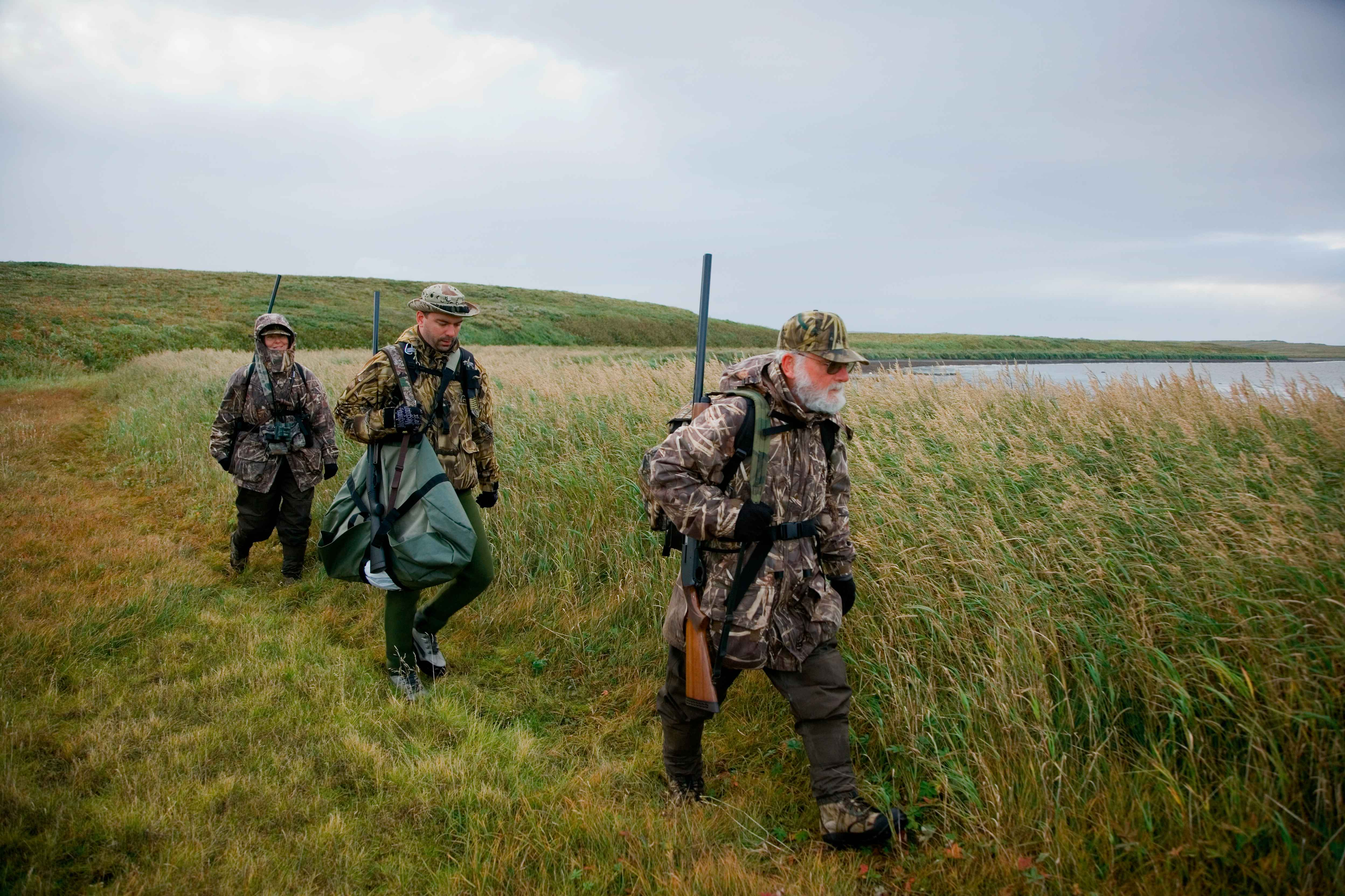380c0c3dd2671 Three waterfowl hunters donned in camouflage and armed with shotguns.