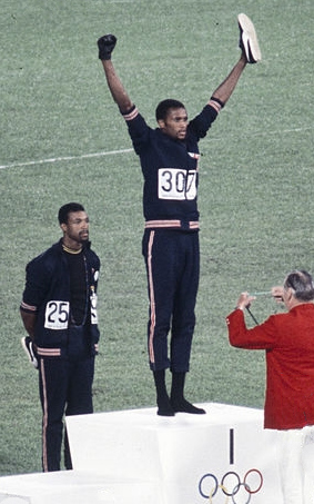 Tommie Smith, born 6 June 1944, at the 1968 Olympic medal ceremony where he and John Carlos (behind) protested against racism. John Carlos, Tommie Smith 1968.jpg
