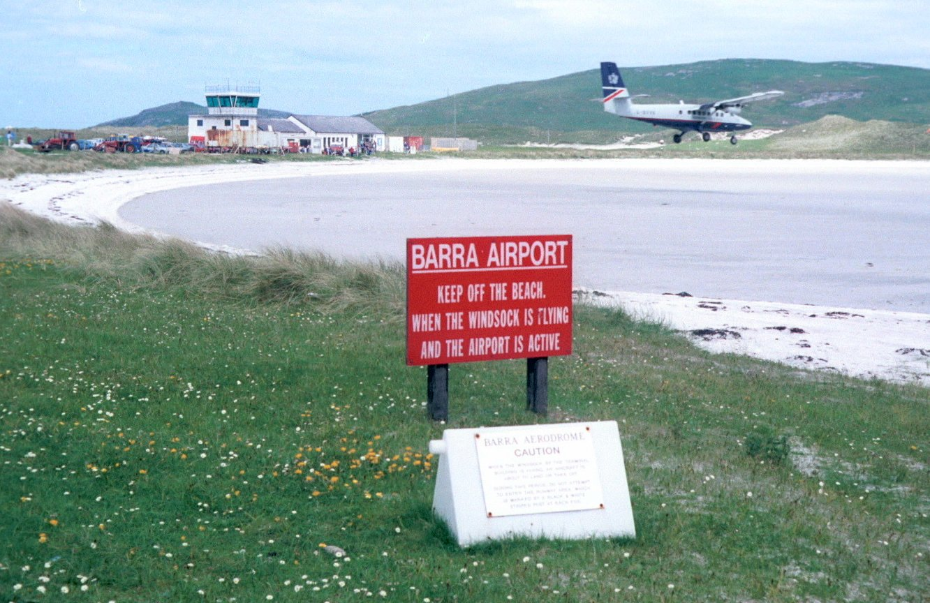 "Photograph: A de Havilland Canada Twin Otter in the colors of British Airways arriving at Barra, Scotland, in 1998. In the background is the control tower, the passenger terminal and luggage processing equipment. The sign in the foreground reads: ""Keep off the beach when the windsock is flying and the airport is active."" Photo credit: James Grey (original license, of the photo only, obtained at: http://creativecommons.org/licenses/by-sa/3.0/deed.en), via Wikimedia Commons. Sign text reproduced with permission from Michael Galbraith, Barra Airport Station Manager."