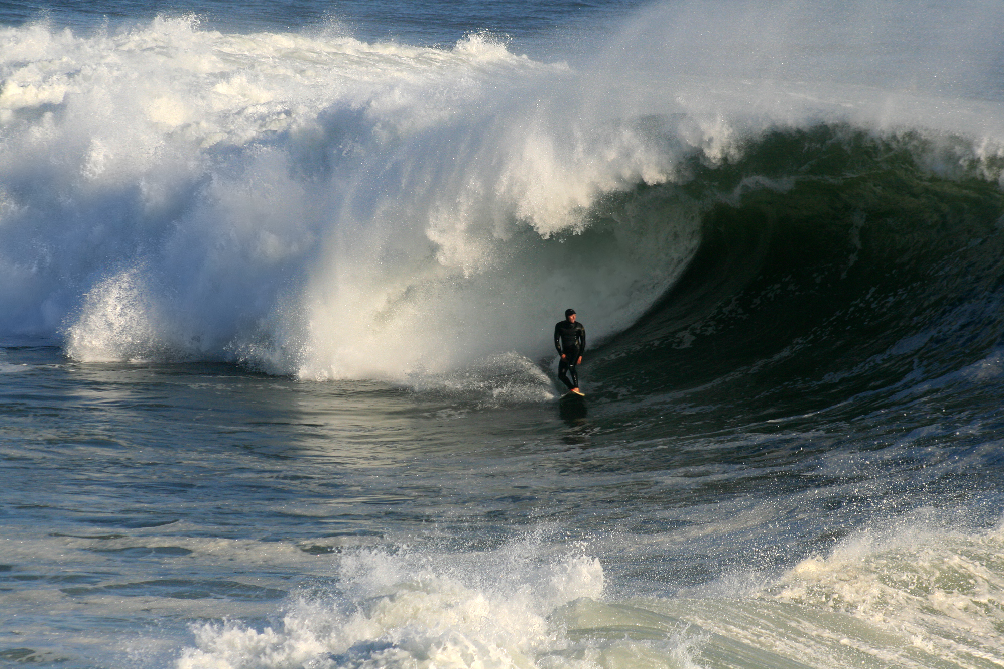 Photo of surfer at bottom of wave, attempting to let tube envelop him