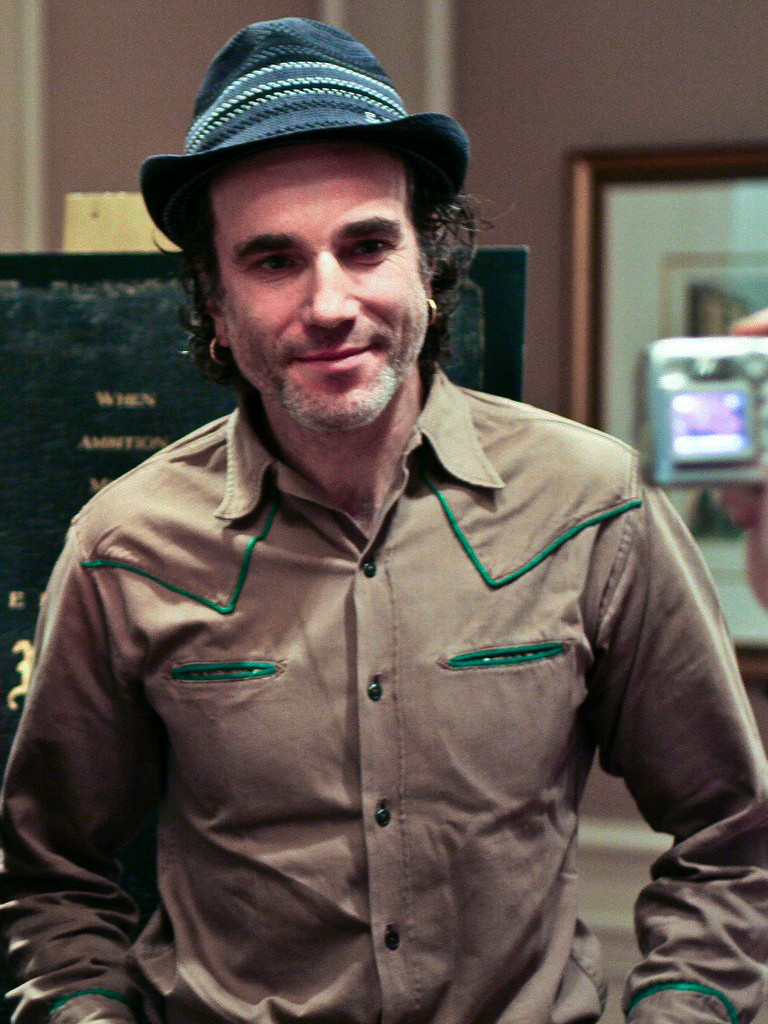 A smiling man wearing a grey hat with piping above the band, and a tan Western style shirt, stands in an office, posing for the camera.