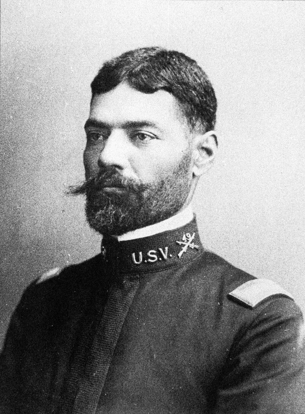 """Head and shoulders of a man with neatly combed hair and a handlebar mustache wearing a plain military jacket with the letters """"U.S.V."""" on the upright collar."""