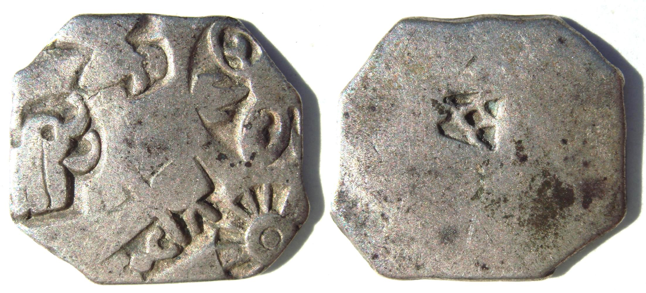 Silver punch mark coin of the Maurya empire, with symbols of wheel and elephant. 3rd century BCE.