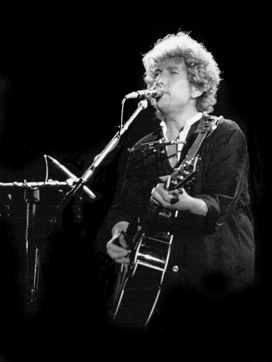 Dylan plays his guitar and sings into a microphone onstage.
