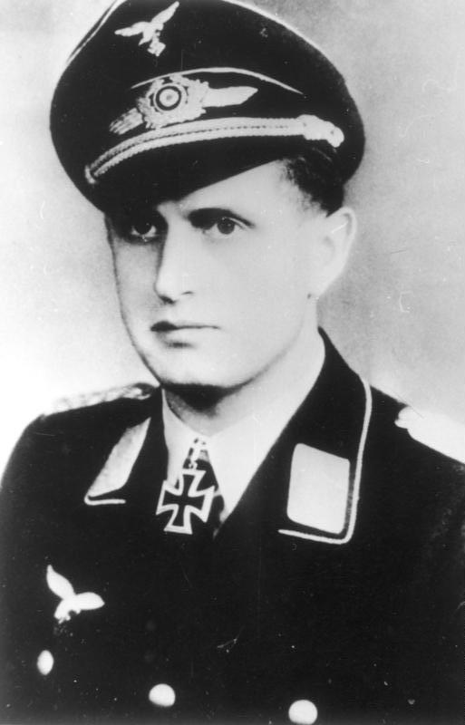 alt=A man wearing a peaked cap and military uniform with an Iron Cross displayed at the front of his uniform collar.