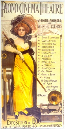 "Illustration of a red-haired woman wearing a large hat, an ankle-length yellow dress, and high heels. She is holding a long baton or swagger stick and leaning against a film projector. A gramophone sits at her feet, the top of the illustration reads ""Phono-Cinéma-Théâtre"". Text to the left of the woman reads ""Visions Animées des Artistes Celèbres"", followed by a list of performers."