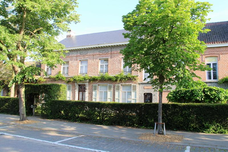 Herenhuis met bijhorende bedrijfsgebouwen (aanvankelijk graanschuren, later paardenstallen) opgericht in de eerste helft  van de 19de eeuw door de familie Vissers.