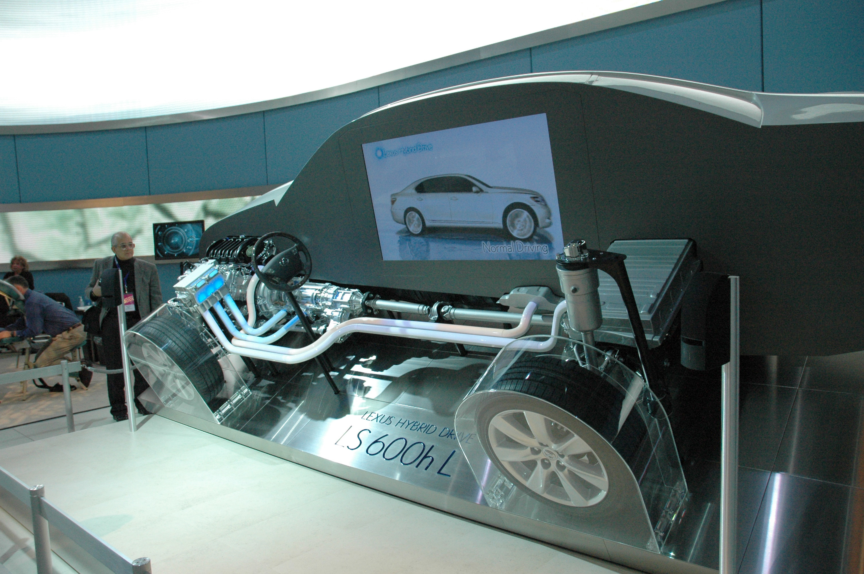 alt=Cutaway hybrid car showing electrical connections; auto show display backdrop.