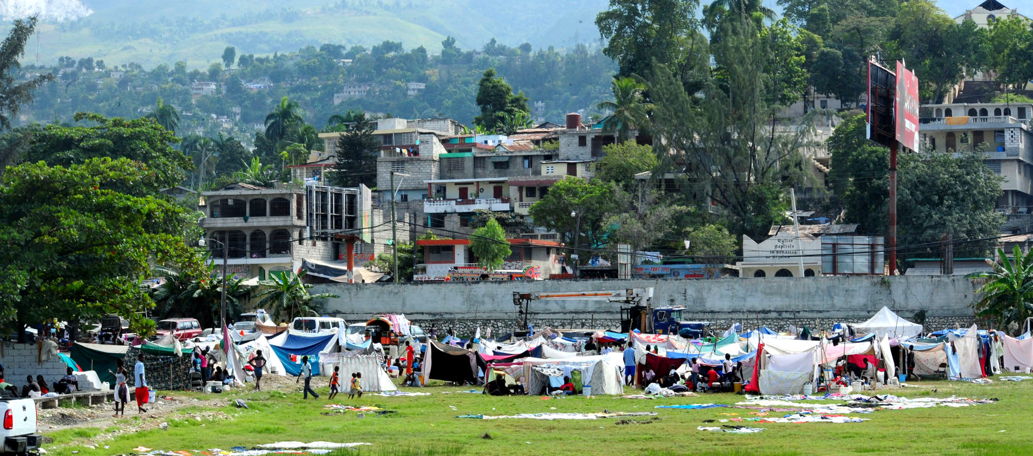 PORT-AU-PRINCE, Haiti (Jan. 16, 2010) Haitian earthquake victims in a tent city wait for medical treatment from U.S. Navy and U.S. Coast Guard personnel. Several U.S. military units, including the aircraft carrier USS Carl Vinson (CVN 70) and Carrier Air Wing (CVW) 17 are conducting humanitarian and disaster relief operations as part of Operation Unified Response after a 7.0 magnitude earthquake caused severe damage near Port-au-Prince on Jan. 12, 2010. (U.S. Navy photo by Mass Communication Specialist 2nd Class Adrian White/Released) Public Domain Mark 1.0