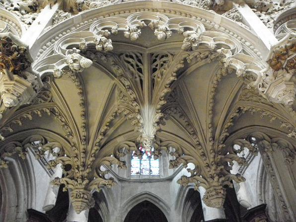 Intricate carvings hang low from arches in a church