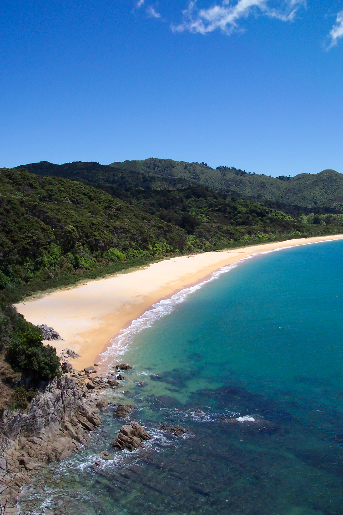Photo showing clear blue water, a golden sanded beach and forested hills