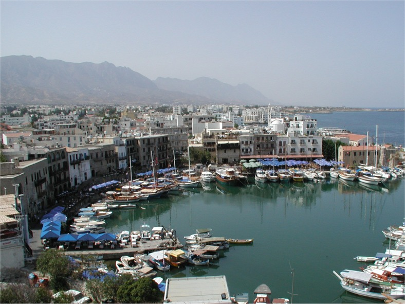 Image of boats in semicircular harbour, low buildings of the village, turquise waters, mountains in the background.