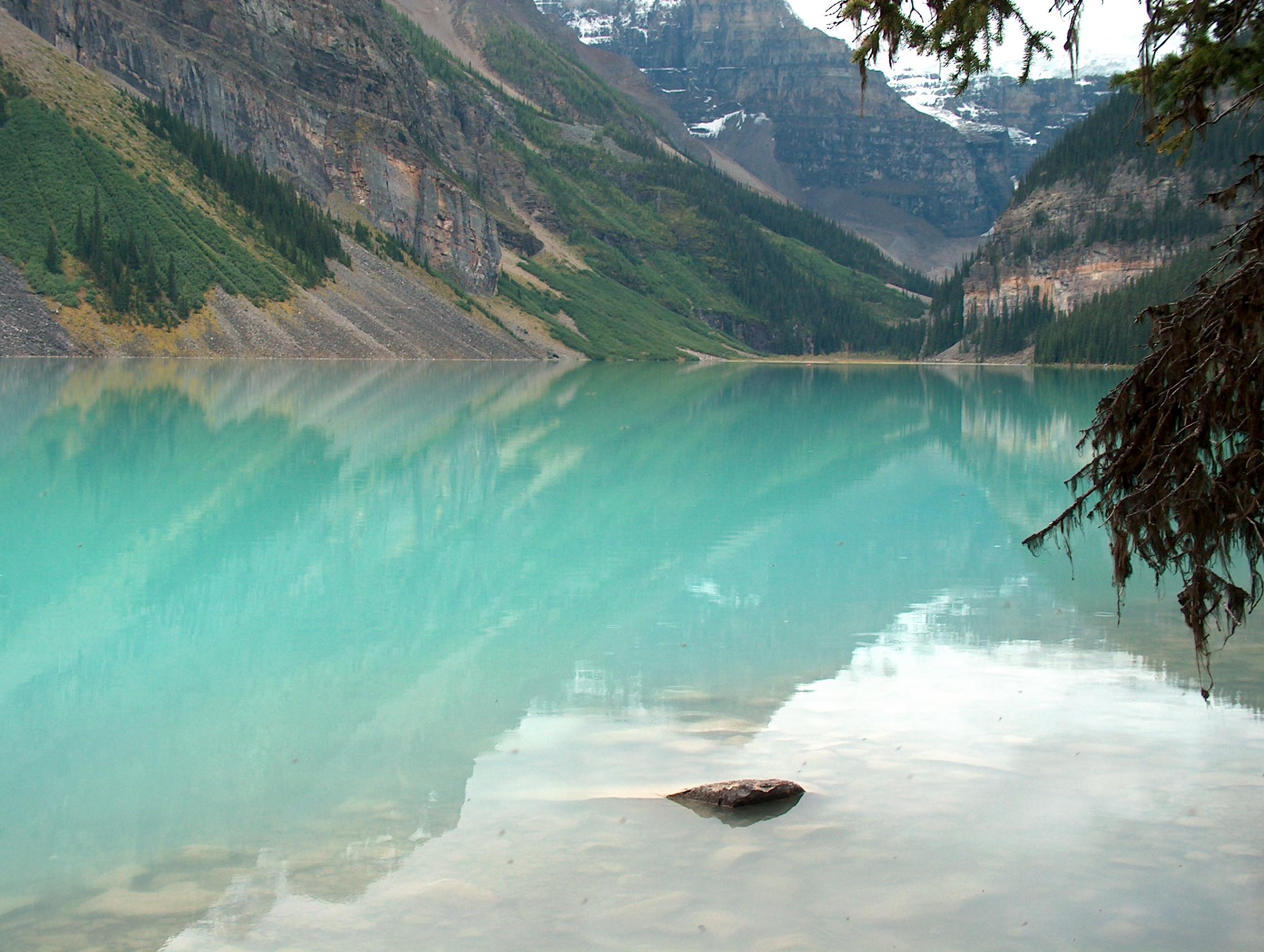 Image of a turqoise lake with mountaneus backdrop