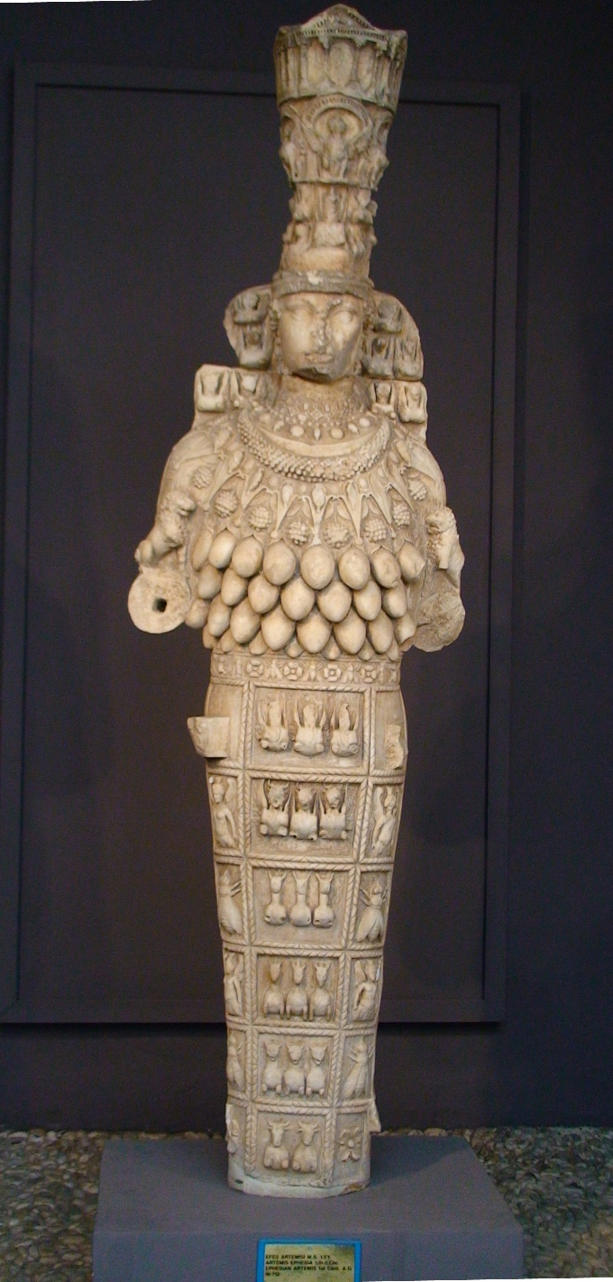 A classic example of the Artemis of Ephesus statue. A woman wearing a crown that is a city, weraing a beaded necklace and a dress composed of wild animals including deer and lions. Where her breasts would appear are numerous, overhanging ellipsoids.