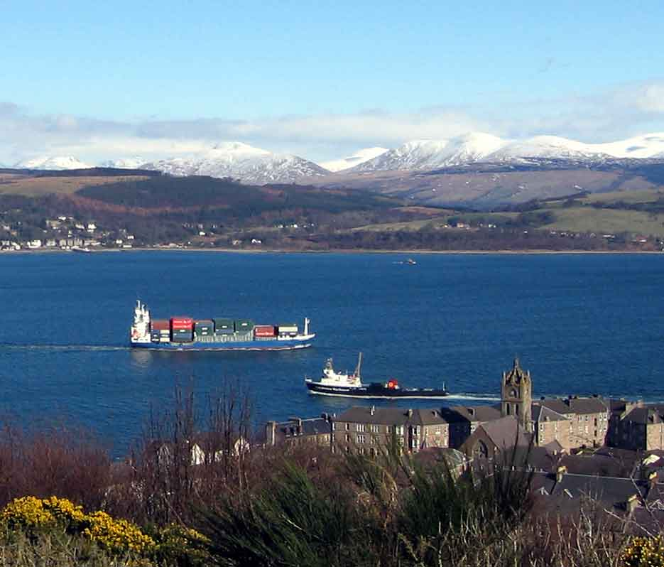 At Gourock a ship heads for the container cranes at Greenock, passing the Caledonian MacBrayne Dunoon ferry. Across the firth <!-- MV --> leaves Kilcreggan for Helensburgh.