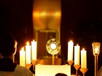 Host displayed in a monstrance, flanked by candles being adored by a kneeling altar server Eucharistic Adoration.jpg