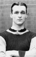 Clean-shaven white man with neatly trimmed hair wearing a dark-coloured knitted sports jersey with light sleeves and collar trim