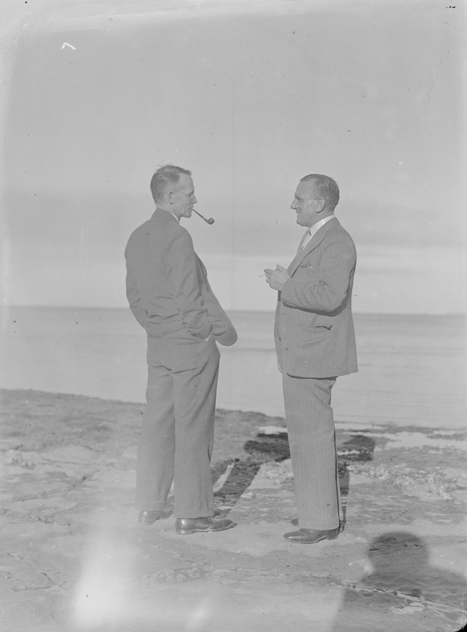 Collins, Tudor Washington, 1898-1970, photographer Title (Two men wearing suits on rock pools) English: They are facing each other.
