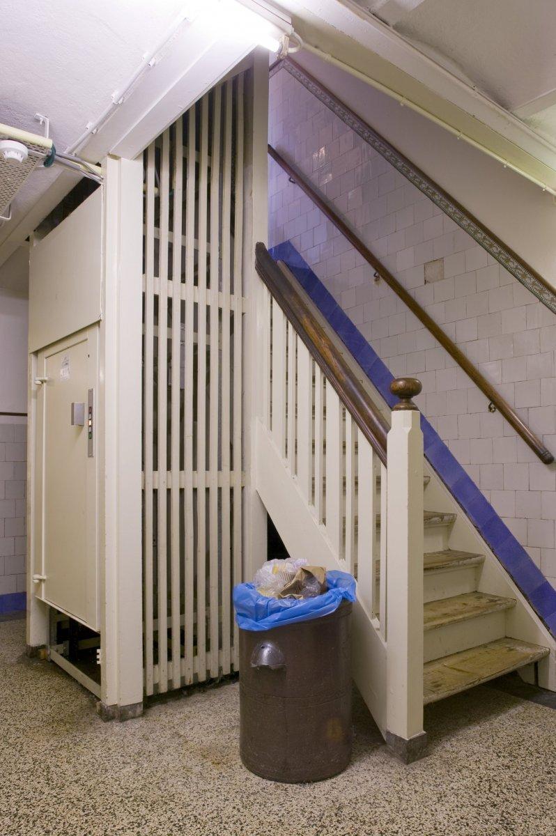 bestandinterieur goederenlift in de kelder met de trap naar de begane grond