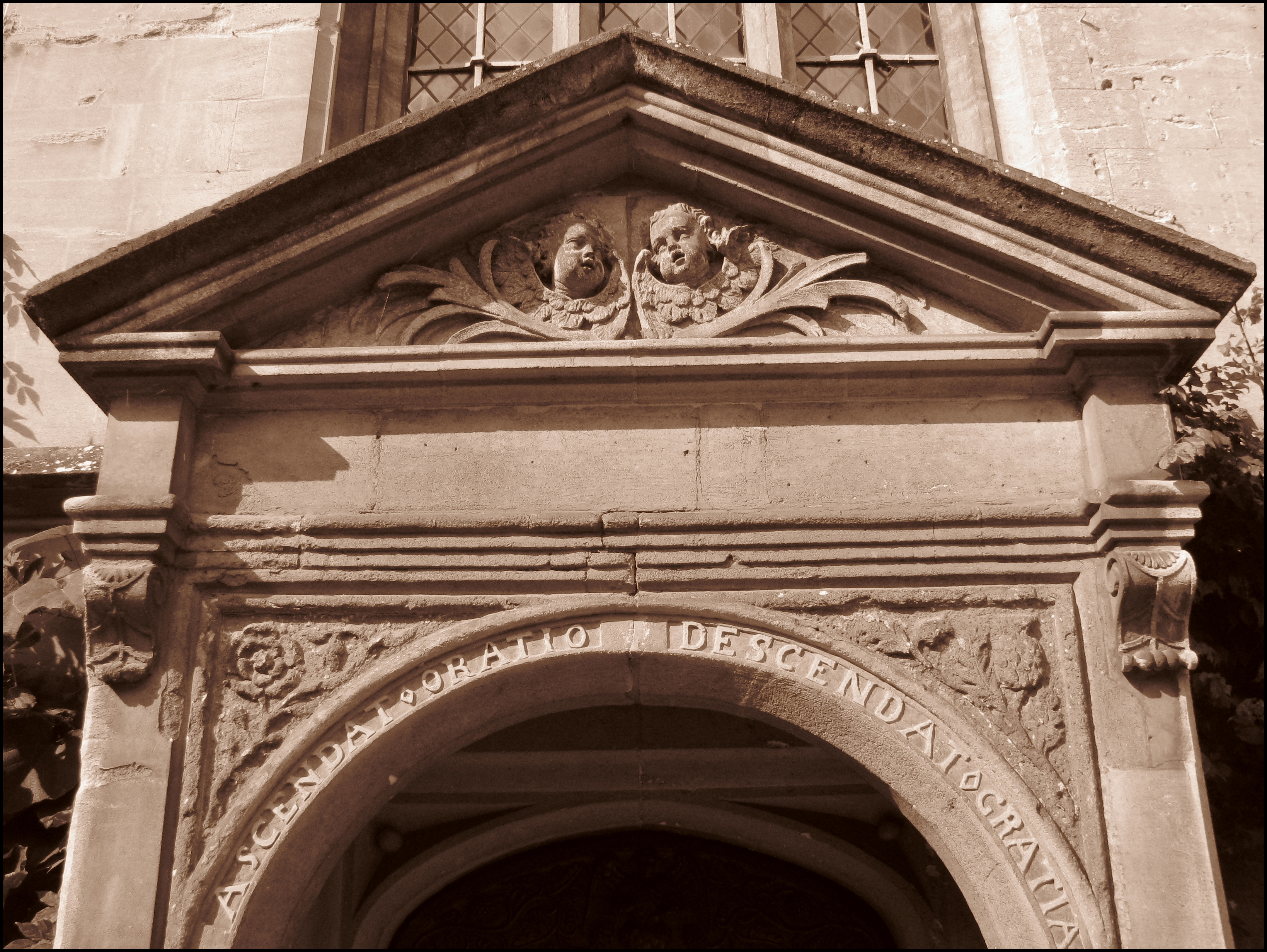 Part of a stone doorway. The top is triangular, with the heads of two