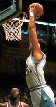 A basketball player slam dunking the ball.