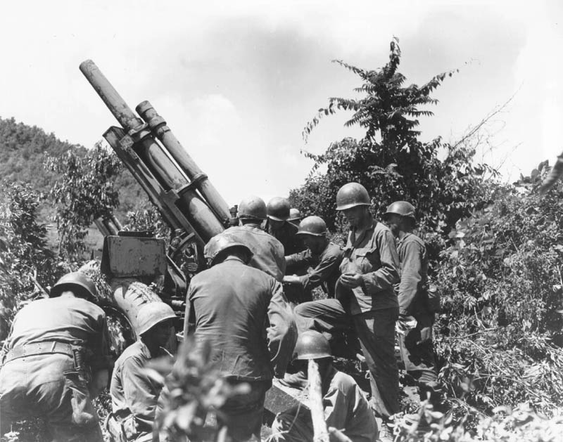 A group of soldiers readying a large gun in some brush